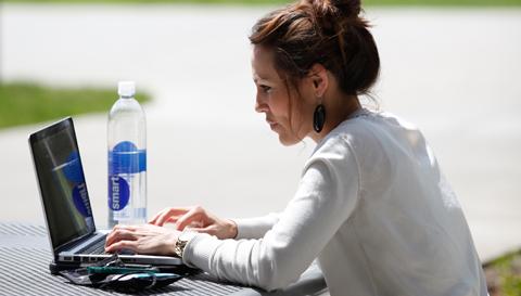 Woman at laptop, outside